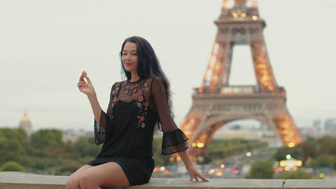 Paris woman smiling eating the french pastry macaron in Paris against Eiffel Footage