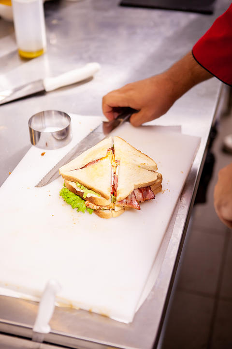 Chef making sandwich in rustic style with bacon and fresh vegetables Photo