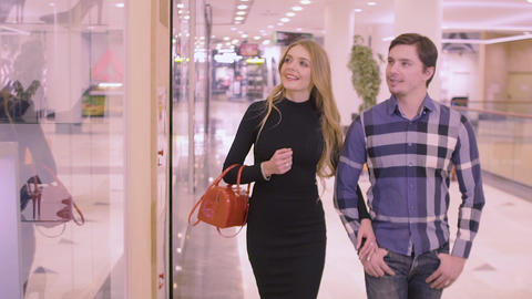 A girl and a guy are walking through the Mall. The girl was interested in the Live Action