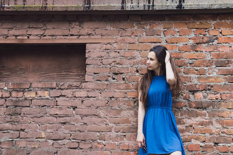 A very beautiful and cheerful girl stands on the street near a brick wall Fotografía