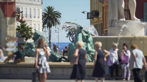 People walking by and taking pictures near Sun Fountain in Nice, city life Live Action