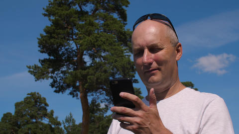Caucasian man browsing mobile phone on green pine background in summer forest Footage