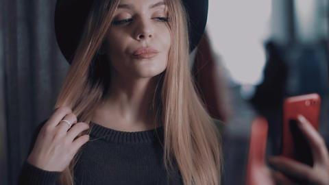 Beautiful blonde in a black hat makes a selfie in a store Footage