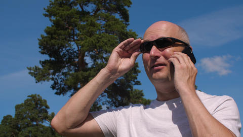 Bald man wearing glasses calling by mobile phone on summer park background Footage