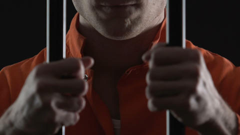 Cruel serial killer holding jail cell bars, prisoner... Stock Video Footage