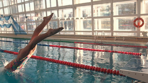 Swimmer at the start jumps into the water in the pool. Water splashes. The Footage