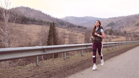 A sporty girl with long hair runs along a mountain road in beautiful countryside Footage