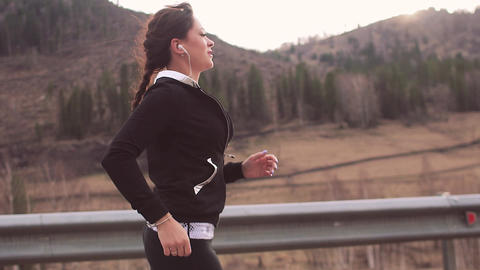 Female running at sunset. Healthy fitness concept. A mountain road at sunset Footage