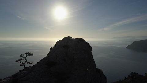 AERIAL SILHOUETTE: young woman climbs up a mountain. Lady reaching the summit in Footage