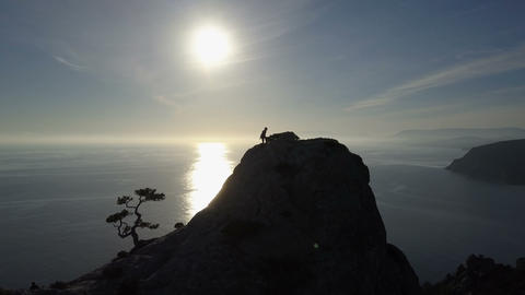 AERIAL SILHOUETTE: young woman climbs up a mountain. Lady... Stock Video Footage