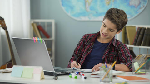 Happy cunning teenager copying homework assignment from internet, cheating Live Action