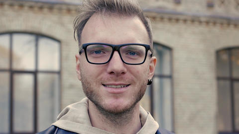 Emotional video-portrait of a nice blue-eyed man with glasses Footage