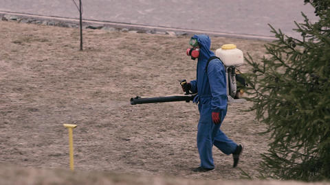 A man in a chemical protection suit and gas mask handles the territory from Footage