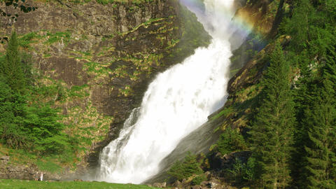 Water spraying from waterfall forming a rainbow Footage
