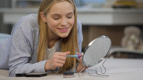 Pretty young lady enjoying her face reflection with lipstick in mirror at home Footage