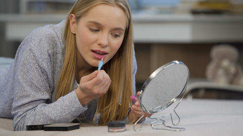 Caucasian female student trying on gloss lipstick near mirror, face beautifying Live Action