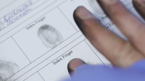 Police officer taking fingerprints of prime suspect, biometric identifier mark Live Action