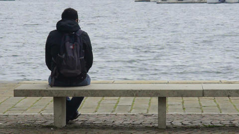 Thoughtful young man sitting on bench and looking at sea, back view, recreation Live Action