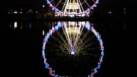 Ferris wheel illuminated with lights at night reflecting on water, entertainment Live Action