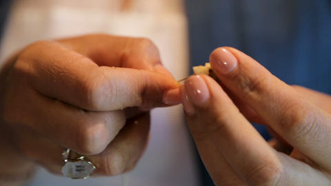 Female hands neatly stringing pieces of Greek nuts on rope, traditional cuisine Footage