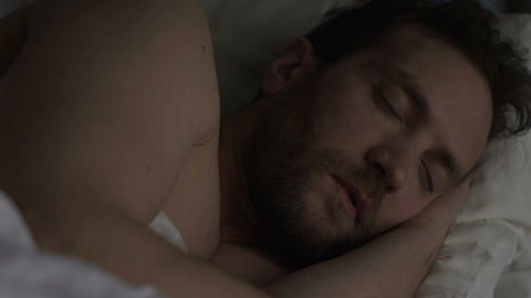 Young man sleeping in bed after exhausting day, healthy sleep, relaxation night Live Action