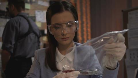 Female detective checking blood knife evidence with fingerprints of killer Live Action