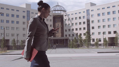 A business woman goes to work and reads an email on her smartphone. Slow motion Footage