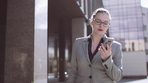 Beautiful Caucasian woman wearing glasses, talking on the phone outdoors on a Footage