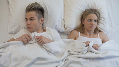 Young man and woman looking embarrassed before first intimacy in bed, insecurity Live Action