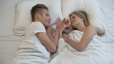 Young couple lying in bed and holding hands, perfect romantic moment, harmony Footage
