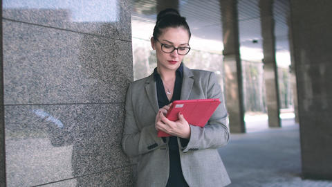 A business woman in glasses uses a tablet PC near the column of the building. 4k ビデオ