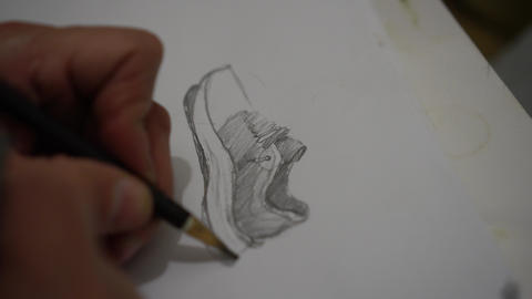 A man making sports shoes sketche by hand Live Action