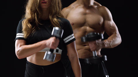 Athletic man and woman flexes their hands with dumbbells, training their biceps Archivo