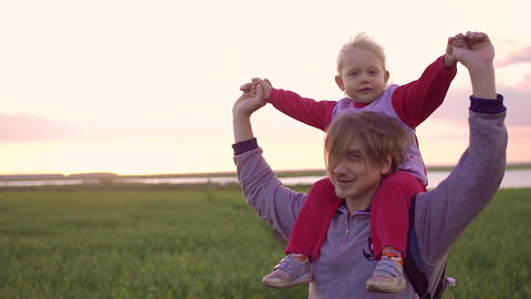 Father carrying daughter on his shoulders and plays with her. During sunset in a Archivo