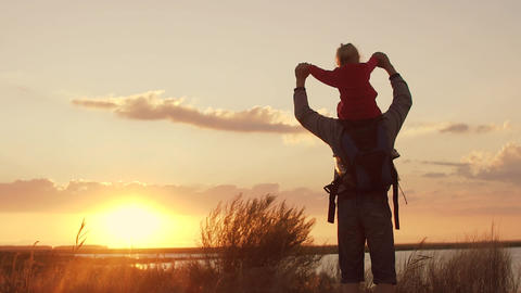 Dad plays with daughter at sunset. Daughter on shoulders of father. Slow motion Footage