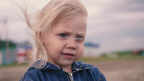 The little blonde girl looking into the distance and holding a sand Footage