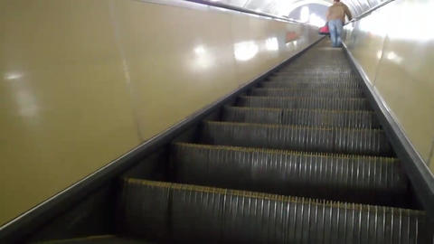 Back view of man with bag is climbing an escalator in the subway. Man in far Footage