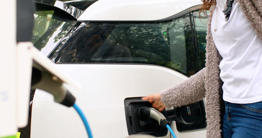 Woman charging electric car at charging station 4k Live Action