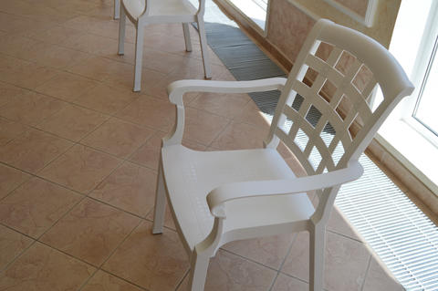 White plastic chair stands in the pool room near the window, the Seating area フォト
