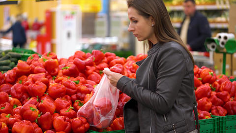Woman chooses red bell pepper in the supermarket Live Action