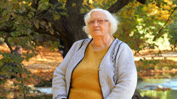 Old woman is resting in park. Autumnal park in the background Footage