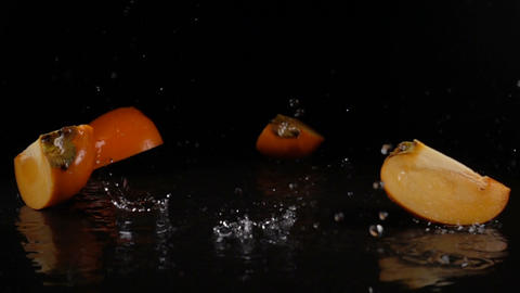 persimmon falls on black surface and breaks into segments 영상물