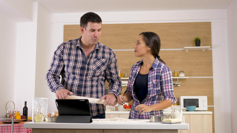 Couple at home looking for recipe on digital tablet PC screen Footage