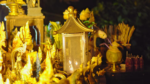 Yellow candles at the buddhist temple in the park at night time, close up Footage