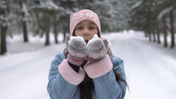 A girl in a good mood blows snow from her hands in the winter forest ビデオ