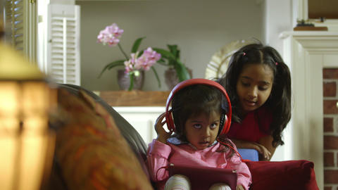 Big sister shares her headphones and tablet with younger sibling Footage