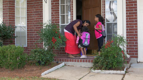 Mother gives kisses to her kids and sends them off to school Footage