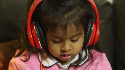 child with headphones captivated by what she hears and sees on tablet pc Footage