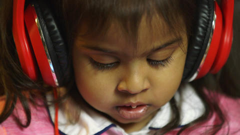 closeup of little girl wearing headphones Footage