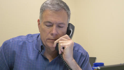 businessman takes a phone call at his desk 4k Footage